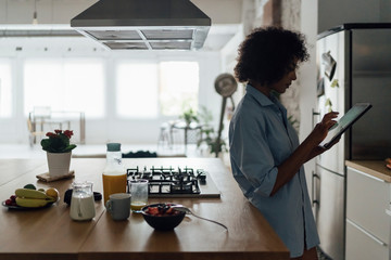 Woman standing in her kitchen, using digital tablet