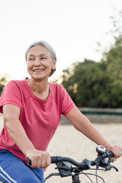 Portrait of smiling senior woman riding bicycle