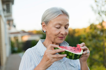 Portrait of senior woman eating watermelon slice in the garden