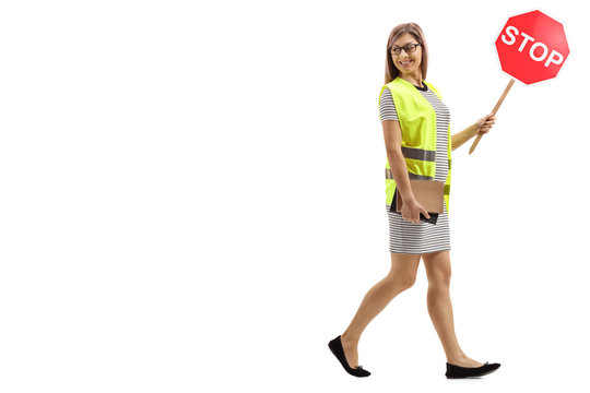 Young woman with safety vest and stop sign walking and looking backwards