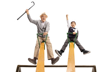 Cheerful grandpa and his grandson having fun on a seesaw