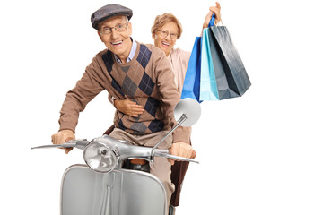 Elderly man and woman with shopping bags riding a vintage scooter