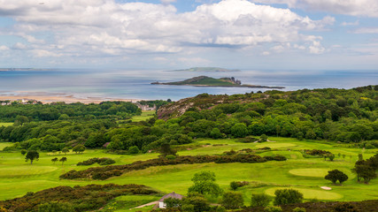 Foto op Canvas Bleke violet Beautiful landscape of green hills covered in grass and trees at the sea shore. View from the Deer Park Golf in Howth, Dublin with the Ireland's Eye, a small island, in the distance.