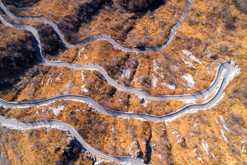 Aerial view of mountain winding road in autumn or winter. Landscape with yellow meadows of dry grass and narrow asphalt road. Top view from flying drone.