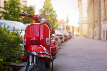 Photo Blinds Scooter Retro red scooter on street of the European city. Summer sun light in background. Copy space beside.