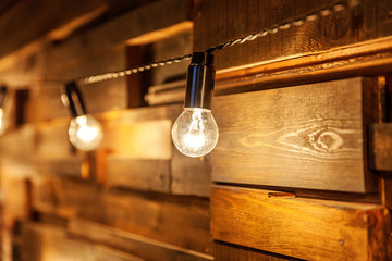 Modern dark classical style interior design apartment with retro lamps hanging light bulbs background. Wooden planks with lamps. Decorated interior room with gold lights. Copy space mockup poster