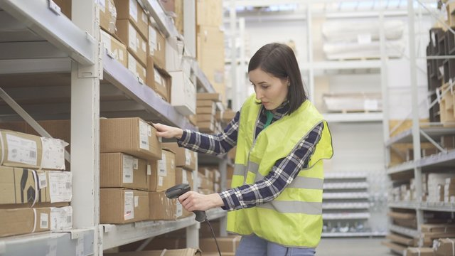 Store worker in the warehouse using a barcode scanner conducts accounting