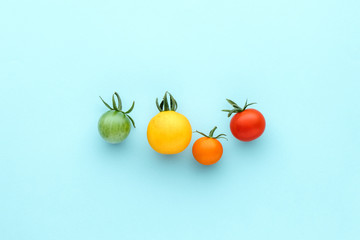 Colorful organic cherry tomatoes on a blue background, creative flat lay healthy food concept, top view