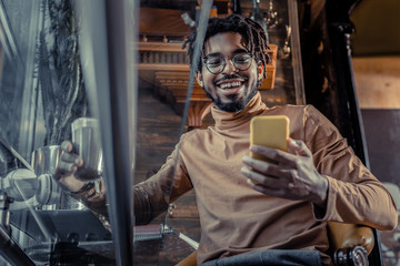 Positive delighted brunette man looking at his gadget