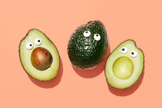 Funny faces avocados on a pastel peach background, creative healthy food concept, top view with clipping path
