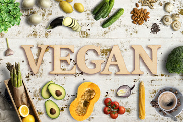 """Word """"vegan"""" in wooden letters with many cooking ingredients"""