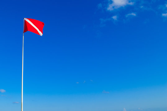 The divers down flag is the internationally recognized notification that there are divers in the water. This one has been shot against a clear blue sky in a topical location