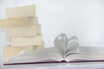 Heart shape from paper book against white background and pile of books