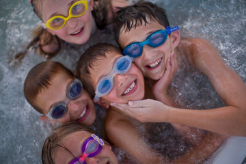 Group of smiling friends sitting in a swimming pool wearing swimming goggles.