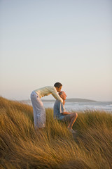 Mid-adult woman giving her seated husband a kiss on the head while on a grassy dune near the beach.