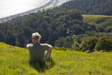 Young man sitting on a grassy hill overlooking a coast in the sunshine.