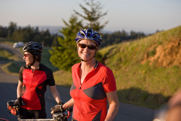 Two smiling women standing with their bicycles at the side of a road in the country.