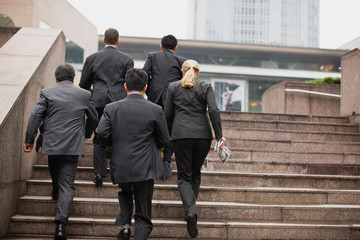 Group of businesspeople walking up a flight of stairs outside a building in the city.