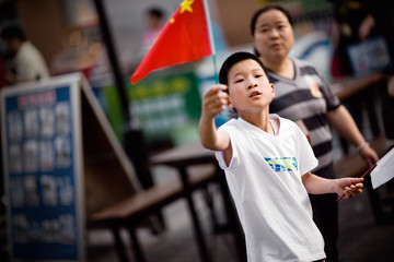 Portrait of a boy holding a flag on the street.