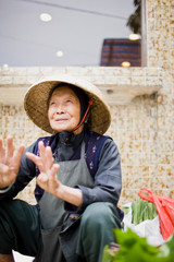 Smiling senior woman crouching in a market place while wearing a hat.