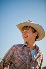 Smiling teenage boy wearing a cowboy hat.