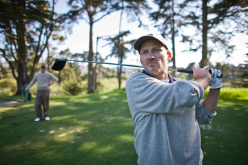 Man holding a golf club over his shoulder while standing on a golf course.