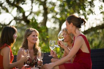 Mid-adult women drinking wind outside.