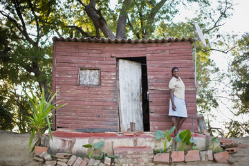 Portrait of a mid-adult woman standing outside a shanty house.