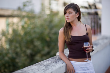 Young adult woman standing on a balcony drinking wine.