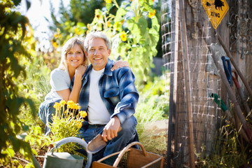 Portrait of a smiling mid-adult couple sitting in their garden in the sunshine.