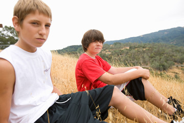 Portrait of two boys sitting on a bank.