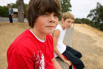 Portrait of two boys sitting on a stone wall.