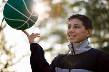 Teenage boy spinning basketball on one finger