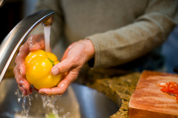 Older woman washing yellow bell pepper