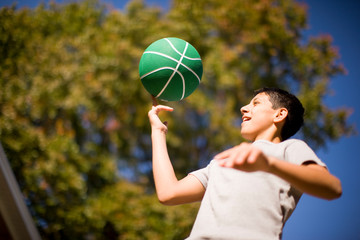 Teenage boy spinning basketball on one finger