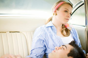 Young couple relaxing in the back seat of a car