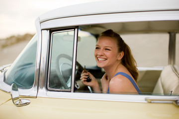 Woman sitting in retro car smiling
