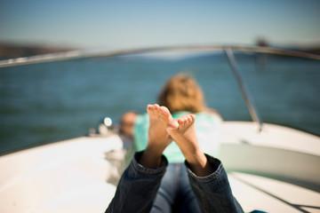 Woman sunbathing on boat deck.