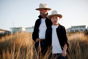 Father and son in cowboy outfits standing in tussock grass.
