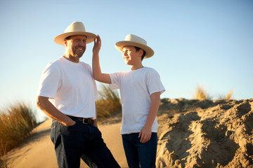 Father and son dressed in cowboy outfits standing on sand dunes.