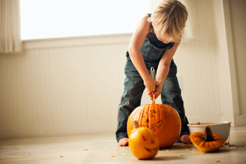 Young boy bends over to use both hands to hold a tool to scrape out the insides of a big pumpkin with a face drawn on it to make it into a Jack O'Lantern like the small one sitting in front of him.
