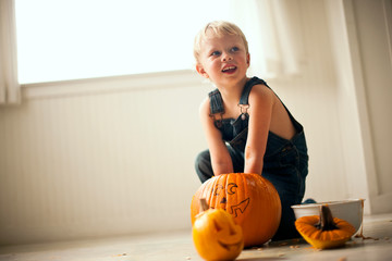 Young boy looks up and smiles as he kneels on a floor and digs both hands into a big pumpkin with a face drawn on it with a bowl and a finished small Jack O'Lantern with a candle lit inside in front of him.