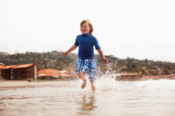Young boy running at water's edge.