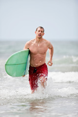 Man running along the beach with his surfboard.