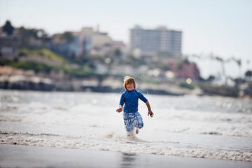 Young boy dressed in blue,  splashing in the ocean.