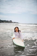 Young woman catching a small wave on her surfboard.