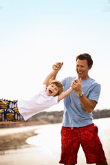 Father swinging son by the arms at the beach.