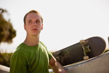 Teenage boy with skateboard at skateboard