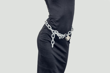 Slim figure girl in black dress. Metal chains on the lock around the waist. Slavery, exploitation of people, lack of freedom, violence.