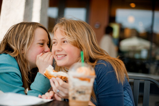 Smiling teenage girl whispering to friend's ear
